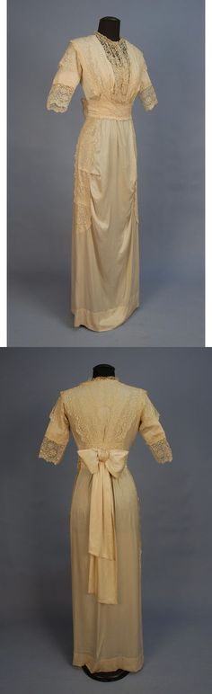 """EDWARDIAN SILK and LACE GOWN. Ivory charmeuse having elbow length sleeve and pleated cummerbund with back bow, skirt with front horizontal tucks, embroidered lace on net decorates the bodice, sleeve and side of skirt. Petersham """"A & M O'Connor, 1242 North Tenth Street Philadelphia"""". B-34, W-22, L-59. excellent. $360."""