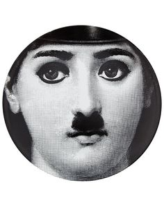 Printed black and white porcelain plate from Fornasetti featuring a woman's face with a Charlie Chaplin moustache and make-up.