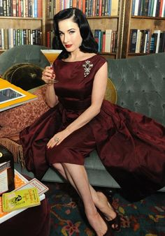 Dita Von Teese in a maroon 50's cocktail dress sipping on some Cointreau