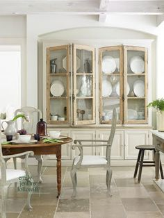 Belgian Style. Interior design by Beth Webb. French Limestone Floors.     Textured wood cabinet by BoBo intriguing Objects has old glass in its unpainted doors. LOVE.