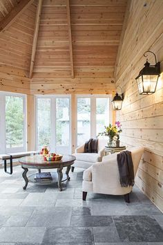 Just off the kitchen, an enclosed porch is comfy most of the year thanks to electric radiant floor warming and glass panels that swap out for screens in warm weather. Shiplap pine decking on the uninsulated walls and vaulted ceiling creates a rustic look.