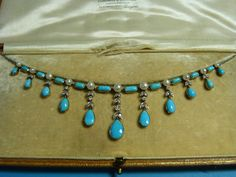 """From Chilcotts in Tiverton, Devon. """"An attractive necklace formed of a row of ten baguette turquoise, with eleven pearls between, suspended from beneath each pearl with eleven teardrop shaped turquoise comprising two outer plain drops then four with a pair of diamond set leaves above, two with a single set diamonds then two leaves, two with three sets of leaves and the centre with two leaves and a single set diamond and then two leaves, all set in yellow gold, suspended from a fine trace…"""