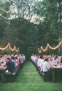 Long picnic tables with twinkly lights hanging overhead | Brides.com