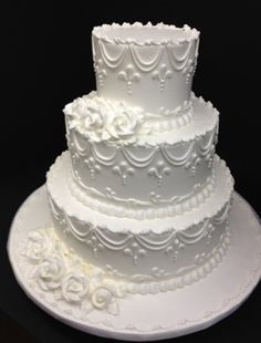 All-White Buttercream Wedding Cake, vintage in-design and scroll work www.millersbakeshop.com