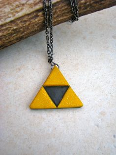 A Zelda Triforce inspired pendant, handmade in polymer clay without the aid of a mould, so it is a unique little creation.