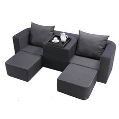 Black & charcoal gray modular sofa with 3 ottomans-can be used as 2 chaises with an arm rest in between or with the center armrest/ottoman used as a third ottoman to create a triple chaise lounge!  Very cool. $699.99 from Brookstone