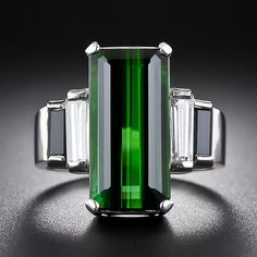 This streamlined modern beauty, sleekly and substantially crafted in platinum, showcases an elongated rectangular, richly saturated green tourmaline. The gemstone is embellished on each side by a slender baguette diamond followed by a baguette onyx set in a classic Art Deco-style stepped arrangement for a chic and dramatic effect. This sleek mid-twentieth century jewel measures 5/8 inch long. $3950