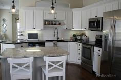 White kitchen with black countertops and stainless steel appliances like my kitchen