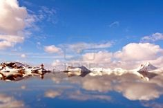 Water reflection of the snowy mountains and the lighthouse in the Arctic Circle