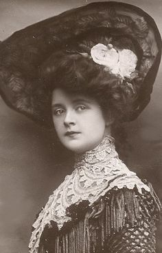 ~1912. Wow, imagine the layers of cloth she is wearing, and that hair and hat~