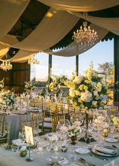 The reception space was illuminated with warm lighting provided by crystal chandeliers that hung overhead and votives which lined tables.