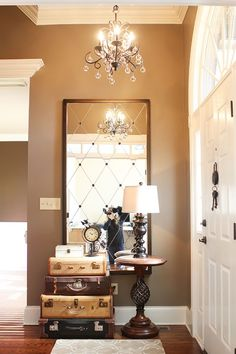 neutral with personality: taupe walls, detailed mirror, and entry table made of vintage suitcases