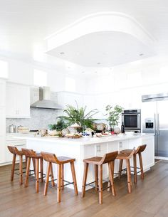 Beautiful white kitchen features an extra large white kitchen island topped with white quartz countertops surrounded on two sides by 6 carved wood counter stools sat on caramel stained wood floors.
