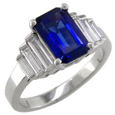 Platinum ring with an emerald-cut sapphire and baguette diamond side stones.