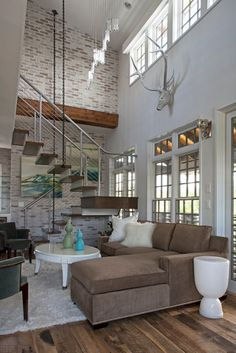 brick accent wall and modern steel staircase in open concept living room