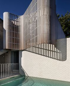 Brick House with Smooth Curves sculptural timber battened screen