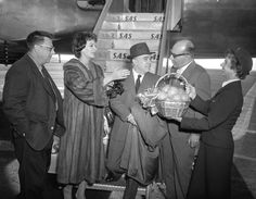 Stewardess presents Actress Sophia Loren with basket of California grapefruit as she and her husband, Producer Carlo Ponti, center, arrive from Copenhagen. On hand to greet pair was Producer Marcello Girosi. Miss Loren will film a comedy here with Actor Anthony Quinn. (Publication: Los Angeles Times - Publication date: January 21, 1958)