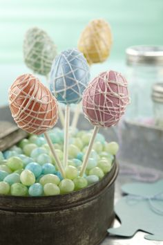 Metallic Easter Egg Cake Pops: Dip and drizzle the egg-shaped cake pops with Candy Melts candy, then paint the lustrous effect of white Pearl Dust.