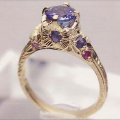 This unique vintage style engagement ring 14kt Yellow Gold setting features  1.25ct Tanzanite and Multi Colored Sapphires (.50ct wt). Hand carved shank. unique artistic design around this unforgettable hand carved ring makes it unlike another. By Maria de la Luz Fine Jewelry  WWW.Shop.MariadelaLuzFineJewelry.com