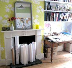 This wallpaper behind the stark white mantel is a grand idea!