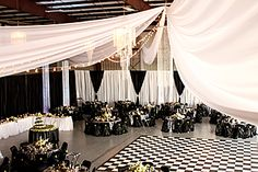 Turning an airport hanger into an elegant wedding reception site with ceiling draping.
