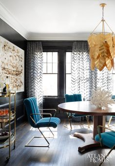 Inspired by the leafy gold chandelier, Stockett and designer Caroline Normark created a posh look in the dining room with a moody color scheme and gilt accents.