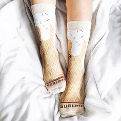 Pés na cama de edredom branco com meias de sorvete de casquinha derretendo
