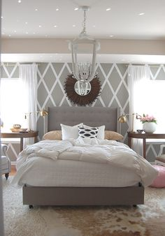 Geometrical Wall Design With Decorative Round Wall Mirror And Upholstered Headboard Bedroom Plus Wall To Wall Carpet