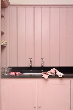 Simple fitted Shaker cupboards painted in 'Old Rose' with sleek polished black granite worktops; a very pretty and refreshing laundry room. Shaker Kitchen, Rustic Kitchen, Pink Laundry Rooms, Hanging Wire Basket, Devol Kitchens, Pink Kitchens, Granite Worktops, Old Rose, Black Granite