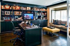 The focal point of this spacious home office is a black built-in bookshelf with a matching desk. A tan sofa is paired with a vibrant yellow striped ottoman, while a window covered wall provides natural light.
