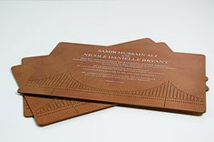 A custom destination wedding invitation resembling perforated copper to mimic the facade of the De Young Museum in San Francisco with a laser cut motif of the Golden Gate Bridge.