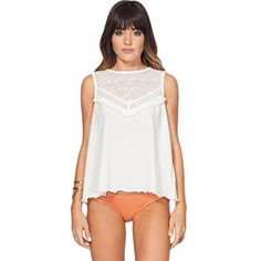This top features mesh jersey fabric a fly-away back with crochet trim and button closure at neck crochet insets at the front and back chest and tassel trim at the front chest....