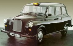 A London Taxi, or to be more precise a Carbodies Fairway. I know 'cos I own and drive one of these, not for a living but just because I love them. Mine is midnight blue though,not black.