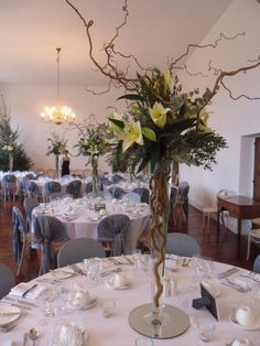 Contemporary trumpet vase display with twisted stems and willow. Perfect height for the Ballroom