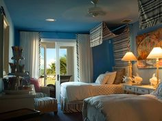 With an ocean-blue ceiling and walls, this breezy kids' bedroom takes after the 2008 HGTV Dream Home's Florida Keys location. Blue and white stripes in the bedskirt, wicker chairs, flowing canopy and curtains add a playful pattern and break up all the solids. Snapper Pinky Cotton Candy, a painting by local artist Stacie Krupa, gives the space a vivid burst of color.