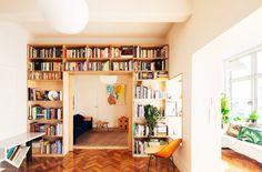A built-in bookshelf wall over a door frame