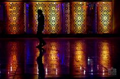 A student passes in front of a lighted frame at the American University of Sharjah Global Day fair.