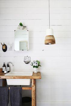 Czy to domek w górach? Niekoniecznie. Bardzo często widujemy bowiem przeniesienie tego stylu nawet do mieszkań i apartamentów. Drewno jest cenione, tak samo jak przyjazne dla oka barwy i ozdoby. Niby całkowite minimum, ale wydaje się, że nic więcej nie ma już sensu dodawać. Świetnie spisuje się nawet lampa sufitowa, która pasuje do ogólnej koncepcji, którą miał tutaj właściciel. #dom #mieszkanie #apartament #łazienka #toaleta #biel #wc ##zlew ##ceramiczny