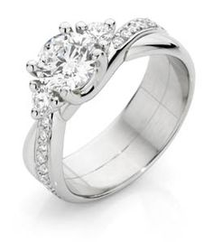 18ct White Gold Diamond Ring      Round brilliant cut centre diamond in a 4 claw setting with a round brilliant cut diamond on either side in a 3 claw setting. Thread and grain set diamonds in either shoulder give a wrap around appearance.      Suits centre diamond from 0.40ct       Can also be made in yellow gold or platinum.