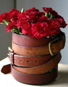Belts wrapped around a vase brings a masculine touch to any table