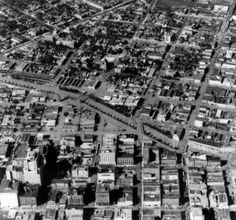 Aerial of 1933 Cherry Creek flood. Aerial view of Cherry Creek floodwater and damage in Denver, Colorado after the Castlewood Canyon Dam break; shows the Auraria neighborhood (upper center), Colfax Street (upper left), Cherry Creek, and downtown buildings.   :: Western History