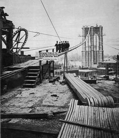 1877: A group of men pose on one of the cables on the Brooklyn Bridge mid-construction. 5,000 strands of steel wire make up the massive cables of the bridge. It took 14 years to complete construction.