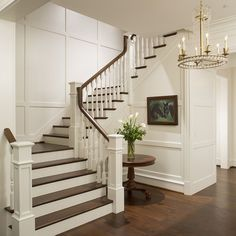 Duvall Creek: Elegant foyer stair wraps a paneled, two-story entry hall. Designed by Purple Cherry Architects.