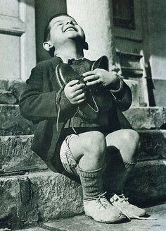 Enfant autrichien qui reçoit des chaussures pendant la 2e guerre mondiale.