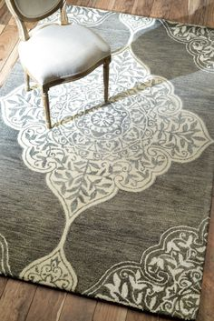 Artfully hand-tufted from wool and art silk, this eye-catching rug lends elegant style to your living room or den.