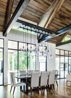 Steel-trimmed windows allow natural light to pour into the dining room, which looks out to the oasis-style pool, designed by J. Brownlee Design in Nashville. A custom industrial light fixture, designed and assembled by Patrick, holds court over the sleek mahogany table.