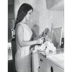 Side profile of a young woman putting clothes into a washing machine Canvas Art - (24 x 36)