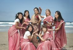 A portrait of the Indian wedding bride and her bridesmaids. The bridesmaids are all wearing pink saris.