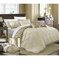This captivating comforter set offers a pintuck design on a solid color block, which reverses to a geometric or floral design. Coordinating pillows complete the look. Crafted of quality microfiber and polyester, this elegant set offers comfort and style.