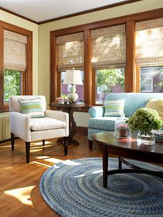 Sunroom Makeover: A round fuzzy chenille rug brings color to the floor, pillows mix things up a bit with assorted textures and patterns, woven shades create soft, dappled light framed by natural oak trim, and the walls are painted in a neutral hue with yellow undertones.